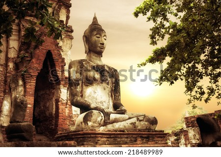 Asian religious architecture. Ancient sandstone sculpture of Buddha at Wat Mahathat ruins under sunset sky. Ayutthaya, Thailand travel landscape and destinations - stock photo