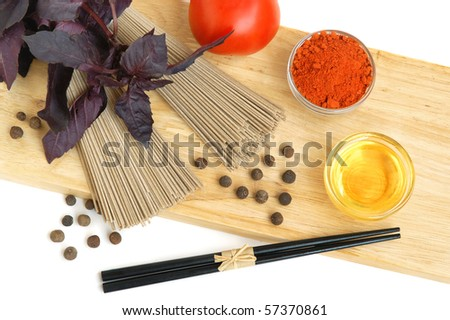 Asian rice and soy noodles with bamboo chopsticks and piles of spices on white background - stock photo
