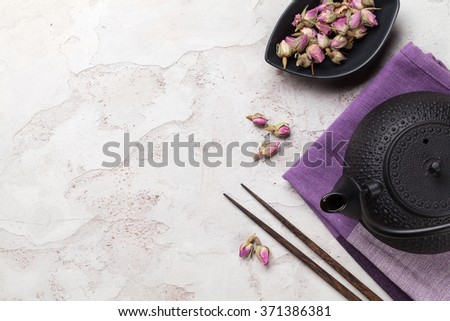Asian rose tea and teapot over stone table. Top view with copy space  - stock photo