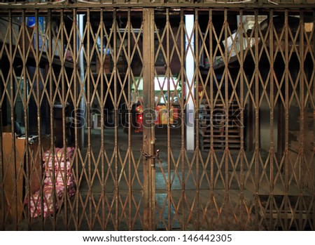 asian rustiness chinese traditional gate or folding doors in the shop with the vintage style - architectural structure in Yau Ma Tei Wholesale Fruit Market in china hong kong - stock photo