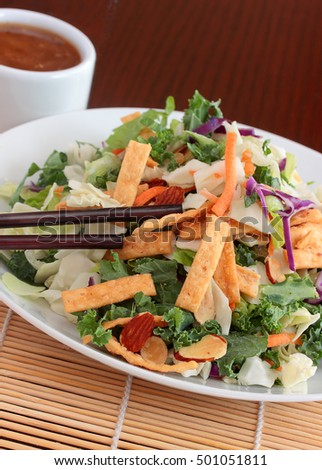 Asian salad.  Fried wontons, red cabbage, kale, romaine lettuce, carrots, and toasted almonds make for a healthy lunch or dinner side.  Served with a light ginger soy sauce
