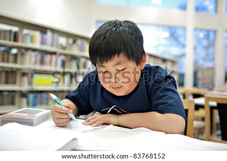 Asian School Boy Working on Homework at Library, Shallow DOF - stock photo