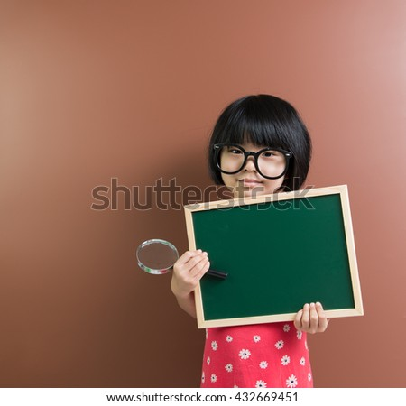 Asian school child hold a blank chalkboard and a magnifying glass for education conceptual