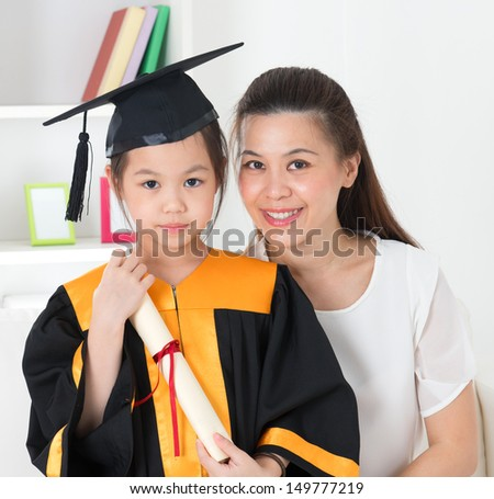 Asian school kid graduate in graduation gown and cap. Taking photo with mother. - stock photo