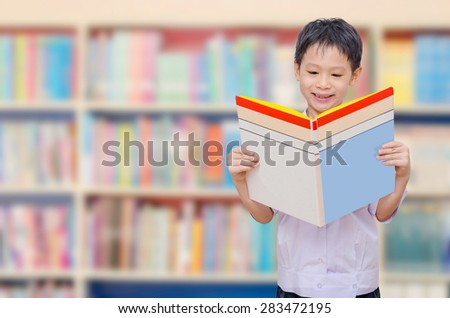 ASian schoolboy in uniform reading book in library - stock photo