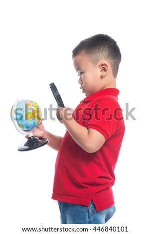 Asian schoolboy with a magnifying glass carefully examines the globe isolated on white background. - stock photo