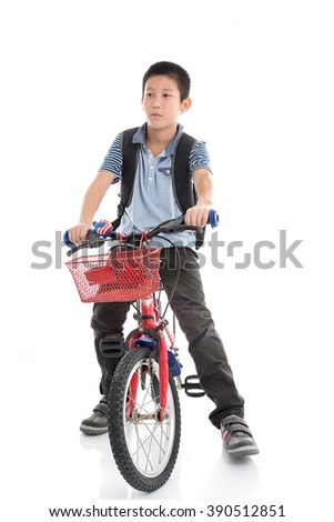 Asian schoolboy with backpack riding a bike isolated on white background - stock photo