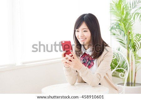 asian schoolgirl using smart phone in the cafe