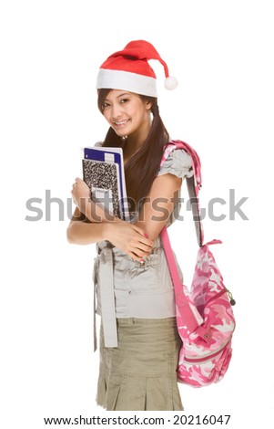 Asian schoolgirl wearing red Santa Claus hat with backpack holding Composition book, notebooks and pen - stock photo