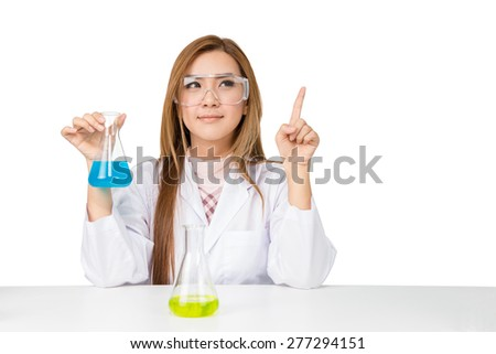 Asian scientific researcher holding at a liquid solution in a lab - stock photo
