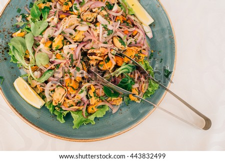 Asian seafood kitchen: marinated mussels salad with onion, lemon and thai sauce (top view) - stock photo