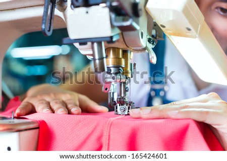 Asian Seamstress or worker in an Asian textile factory sewing with a industrial sewing machine, she is very accurate - stock photo