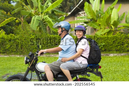 asian senior couple driving motorcycle to travel - stock photo