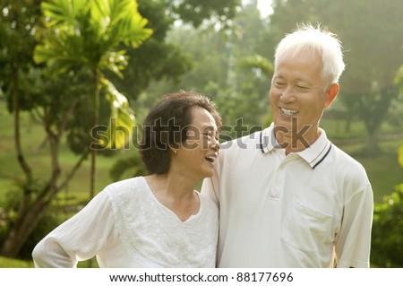 Asian Senior Couple having conversation at outdoor park - stock photo