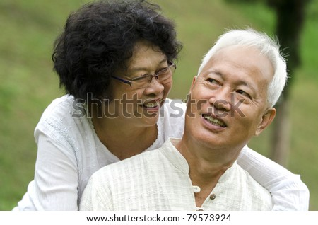 asian senior couple with green natural background