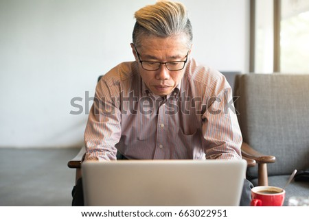asian senior male using laptop on cafe