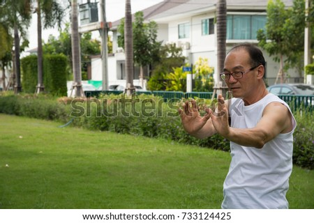 asian senior man wear white shirt stand and practice tai chi on the grass in the garden