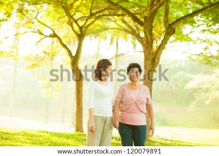 Asian senior mother and adult daughter walking at outdoor green park - stock photo