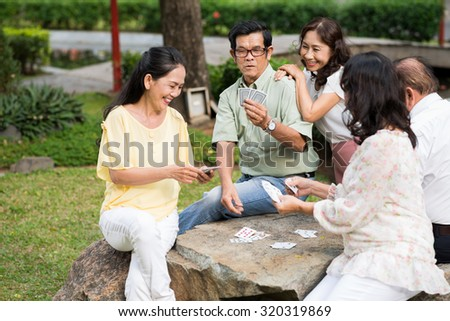 Asian senior people playing cards outdoors - stock photo
