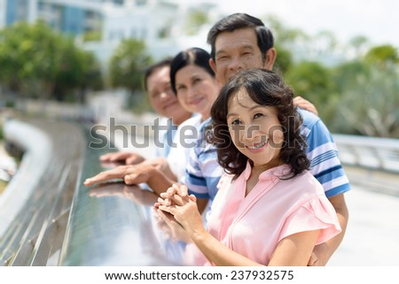 Asian senior people standing in a row and looking at the camera, focus on foreground - stock photo