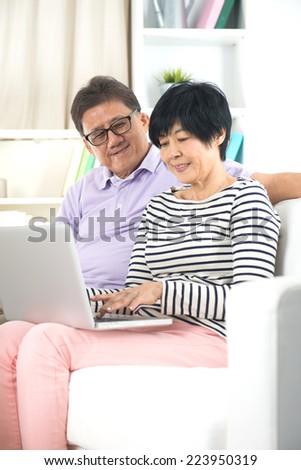 asian senior surfing internet on sofa at home - stock photo