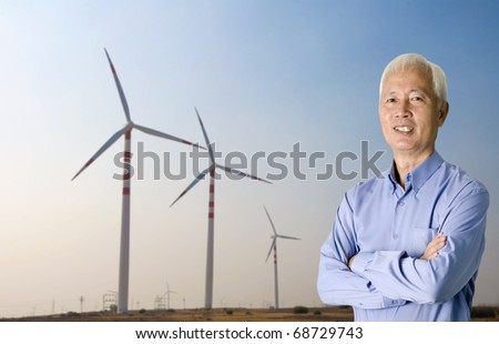asian senior with windmill on the background renewable energy concept photo