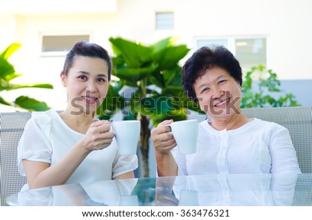 Asian senior woman and daughter enjoying tea time - stock photo