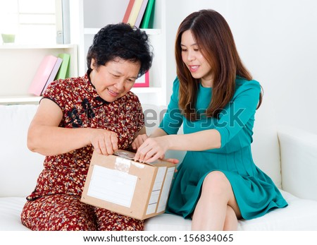 Asian senior woman and daughter opening a courier parcel - stock photo