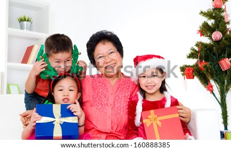 Asian senior woman and her grandchildren celebrate christmas - stock photo
