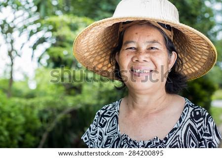 Asian senior woman at park, thailand woman smiling happily. - stock photo