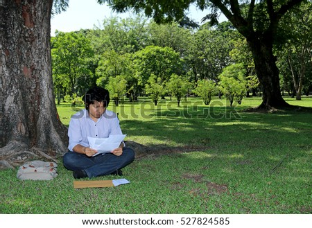 Asian serious man sitting under the tree and read documents in the public garden