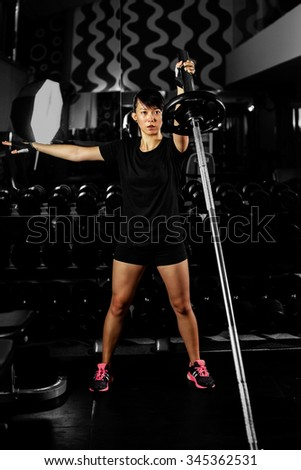 asian sexy fitness girl  weightlifting in gym with heavy weights on black background - stock photo