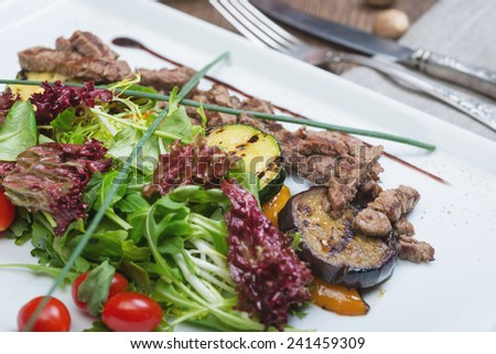 Asian Sliced Beef Salad with vegetables and herbs on the wooden table