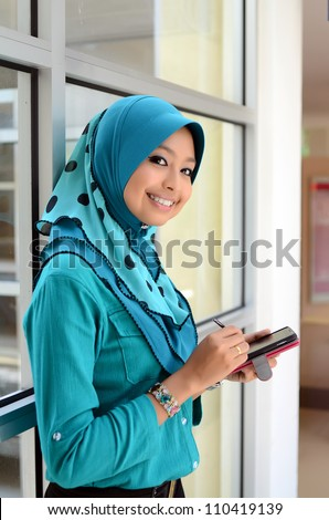 Asian smiling business woman working with mobile phone notepad - stock photo