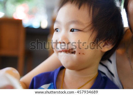 Asian smiling kid eating chocolate at coffee shop with his mom. Smeared stained with chocolate lips