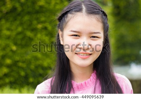 Asian smiling little girl sitting in the park.