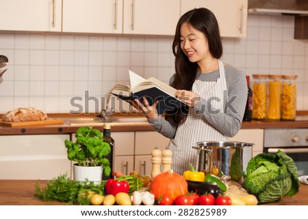 Asian smiling woman looking a cookbook while standing in her kitchen - stock photo