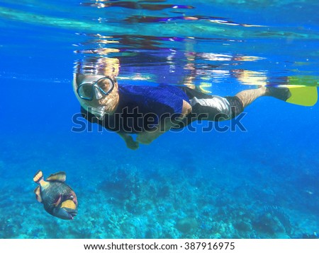 Asian snorkel and big fish under blue water during snorkeling lesson near coral reef, Bali, Indonesia - stock photo