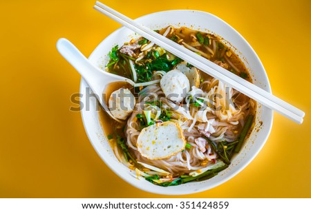 Asian soup with fish balls, fresh herbs and rice noodles in a bowl with chopsticks close-up. top view
