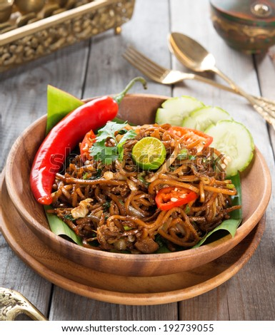 Asian spicy fried noodles, ready to serve on dining table. - stock photo