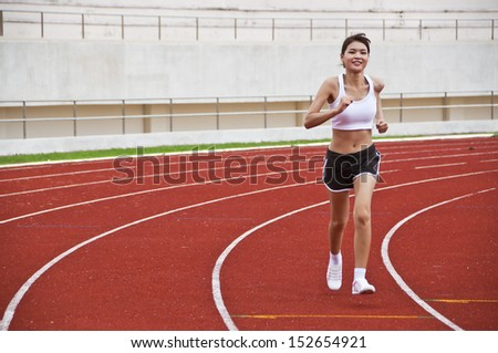 Asian sport girl exercise in public national stadium.