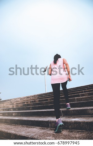 Asian sporty woman running outdoors in park from back angle,Thai female run up stair in the evening,Young lady heathy lifestyle