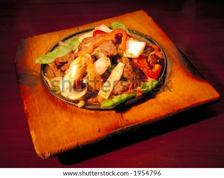 asian stir fry dish on sizzling hotplate - stock photo