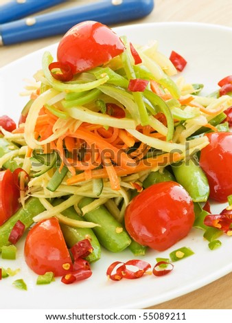 Asian stir-fry with green peas, tomatoes, ginger, carrot, cucumber and chili peppers. Shallow dof. - stock photo