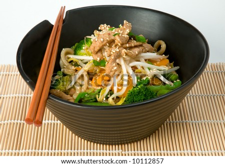 Asian stir fry with Shanghai noodles, pork, vegetables, bean sprouts and sesame seeds, with chopsticks on bamboo mat - stock photo