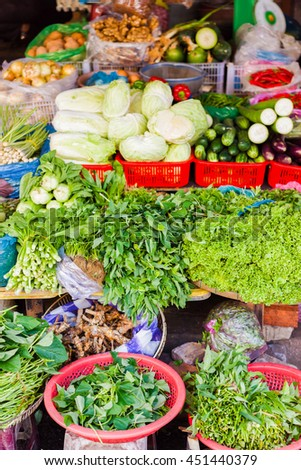 Asian street farmer market selling fresh vegetables in Hoi An, Vietnam. Cabbage, cucumber, zucchini and sprouting onion. Mainly green colors.