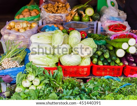 Asian street farmer market selling fresh vegetables in Hoi An, Vietnam. Cabbage, cucumber, zucchini and onion. Mainly green colors.