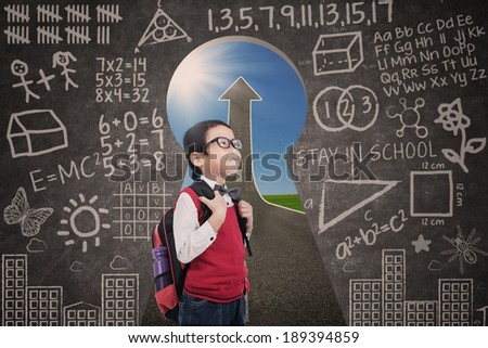 Asian student boy standing in class with success road view from keyhole - stock photo