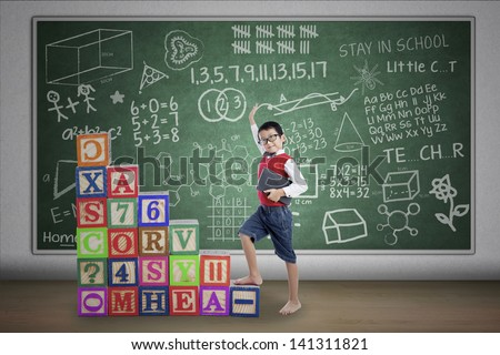 Asian student boy stepping on crossword in class - stock photo