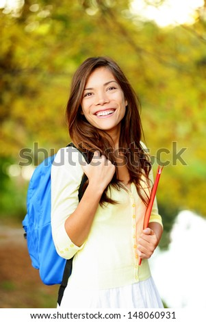 Asian student girl back to school university. Beautiful woman holding books in autumn background. Asian student girl on university college campus park smiling happy. Mixed race Asian Caucasian girl. - stock photo